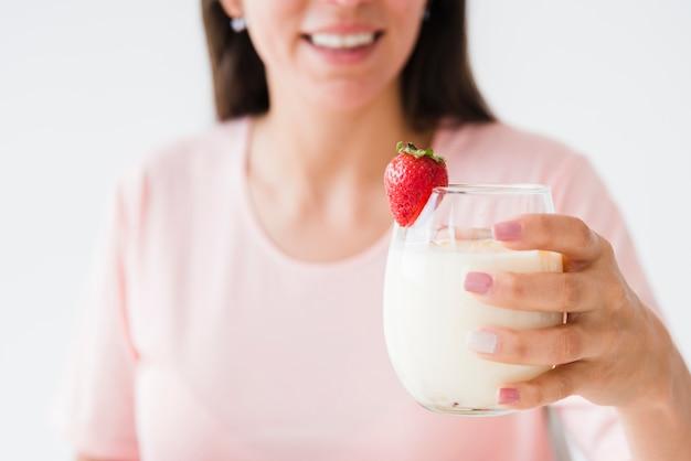 Nahaufnahme einer lächelnden jungen frau, die joghurtglas mit erdbeere hält Kostenlose Fotos