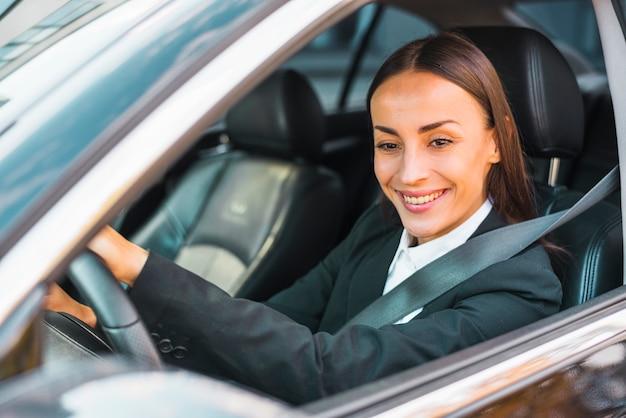 Nahaufnahme einer lächelnden jungen geschäftsfrau, die ein auto antreibt Kostenlose Fotos