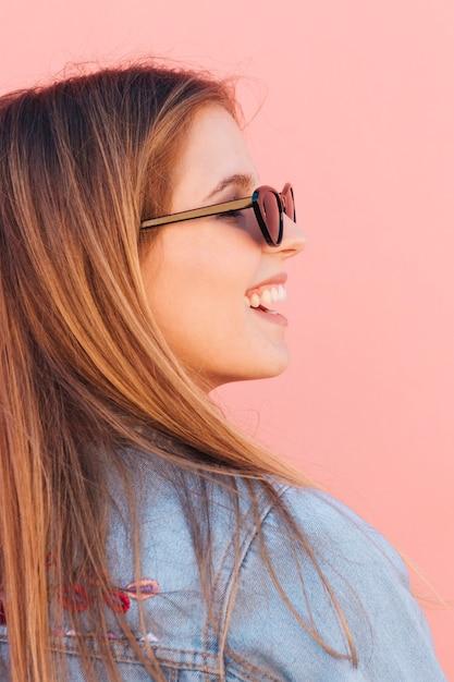 Nahaufnahme einer lächelnden tragenden sonnenbrille der jungen frau gegen rosa hintergrund Kostenlose Fotos