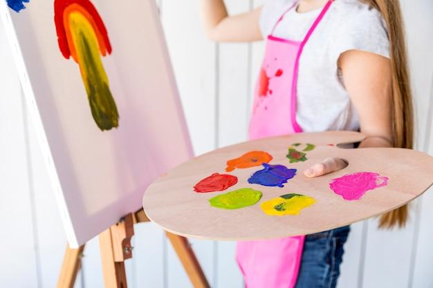Nahaufnahme einer mädchenmalerei auf dem segeltuch, das in der hand mehrfarbige hölzerne palette hält Kostenlose Fotos
