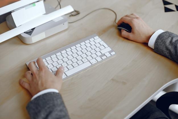 Nahaufnahme einer männlichen hände beschäftigt, die auf einem laptop tippt. mann im büro. Kostenlose Fotos