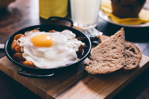 Nahaufnahme einer mahlzeit bestehend aus ei, toast und bohnen auf einem holzbrett Kostenlose Fotos