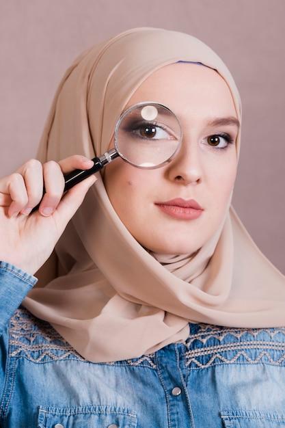 Nahaufnahme einer moslemischen frau, die durch lupe schaut Kostenlose Fotos