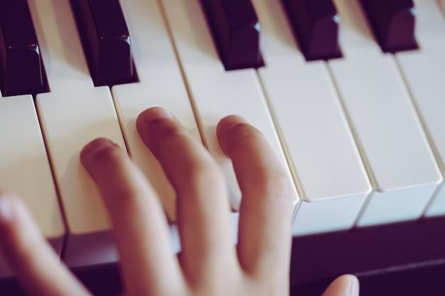 Nahaufnahme einer musik hand der kinder, die das klavier spielt Premium Fotos