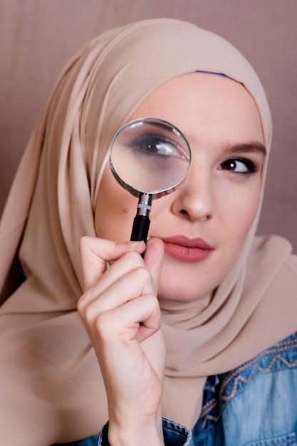 Nahaufnahme einer neugierigen moslemischen frau, die durch lupe schaut Kostenlose Fotos