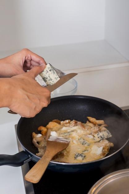 Nahaufnahme einer person, die den käse in der pfanne schneidet Kostenlose Fotos