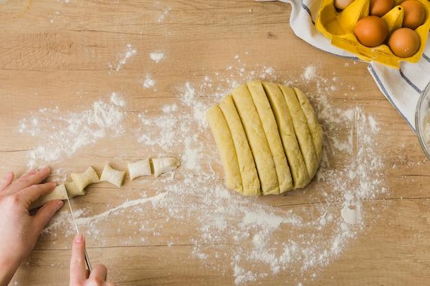 Nahaufnahme einer person, die den teig für das zubereiten der frischen italienischen teigwaren gnocchi schneidet Kostenlose Fotos