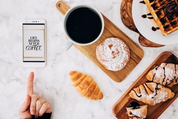 Nahaufnahme einer person, die finger auf mobiltelefon mit mitteilung und frühstück auf strukturiertem marmorhintergrund zeigt Kostenlose Fotos