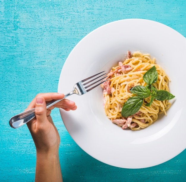 Nahaufnahme einer person, die spaghettis mit gabel auf türkishintergrund isst Kostenlose Fotos