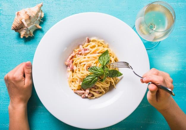Nahaufnahme einer person, die spaghettis mit weinglas und tritonshorn auf türkishintergrund isst Kostenlose Fotos