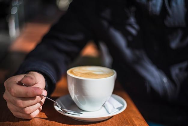 Nahaufnahme einer person mit cup heißem espressokaffee auf tabelle Kostenlose Fotos