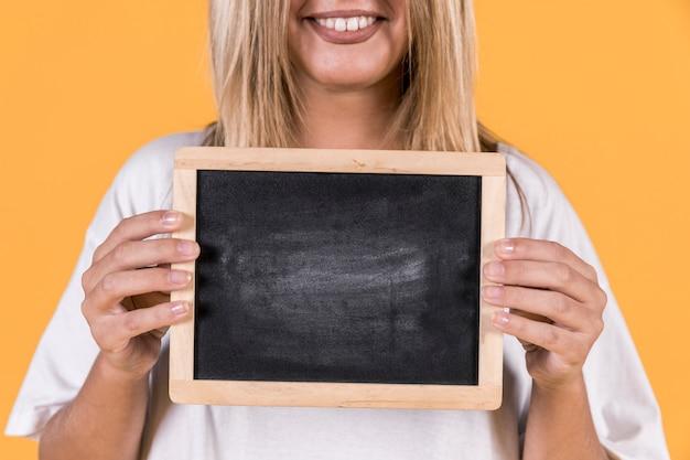 Nahaufnahme einer tauben frau, die mit leerem schiefer über gelbem hintergrund steht Kostenlose Fotos