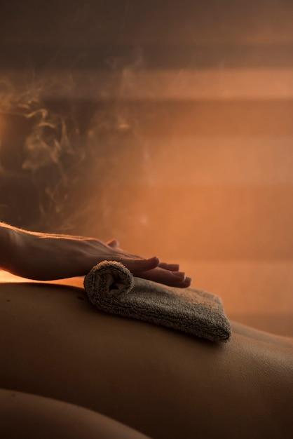 Nahaufnahme einer therapeuthand, die rückseite der frau mit heißem tuch im badekurort massiert Kostenlose Fotos