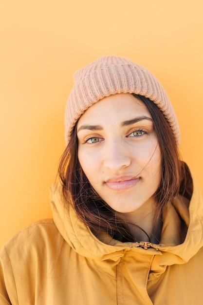 Nahaufnahme einer tragenden strickmütze der hübschen frau, die kamera betrachtet Kostenlose Fotos
