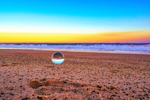 Nahaufnahme einer transparenten kugel auf dem sand, der durch das meer während des sonnenuntergangs am abend umgeben ist Kostenlose Fotos