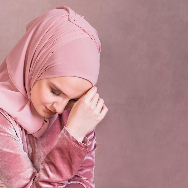 Nahaufnahme einer traurigen arabischen frau gegen studiooberfläche Premium Fotos