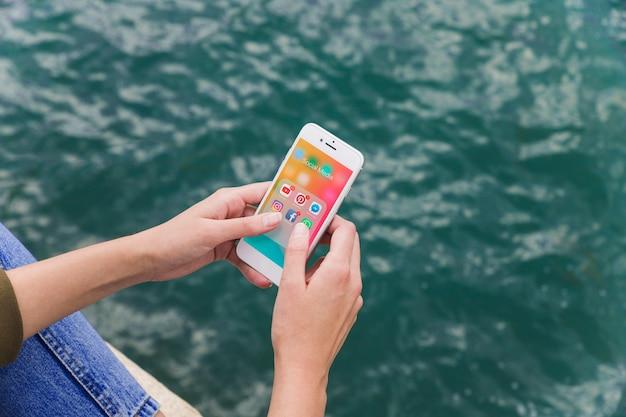 Nahaufnahme einer weiblichen hand unter verwendung des mobiltelefons mit social media-benachrichtigungen auf schirm Kostenlose Fotos