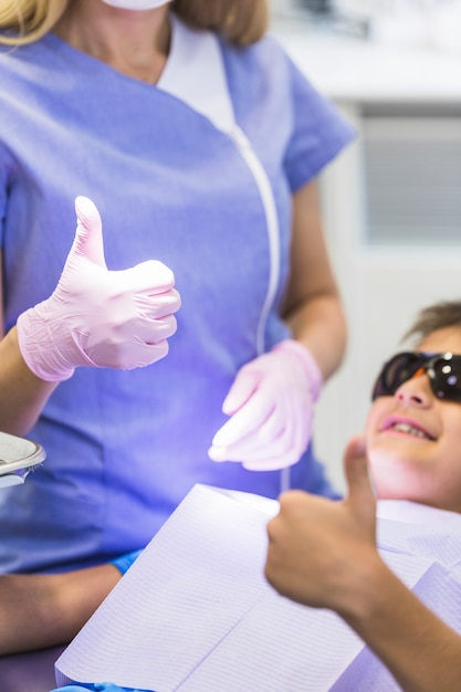 Nahaufnahme einer zahnarzt- und jungenhand, die oben daumen gestikuliert Kostenlose Fotos