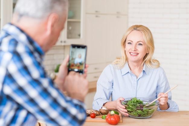 Nahaufnahme eines älteren mannes, der foto ihrer frau macht frischen salat in der glasschüssel zubereitet Kostenlose Fotos