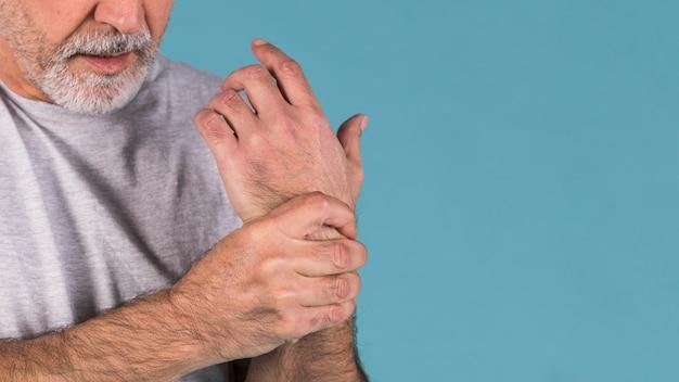 Nahaufnahme eines älteren mannes, der ihr schmerzliches handgelenk hält Kostenlose Fotos