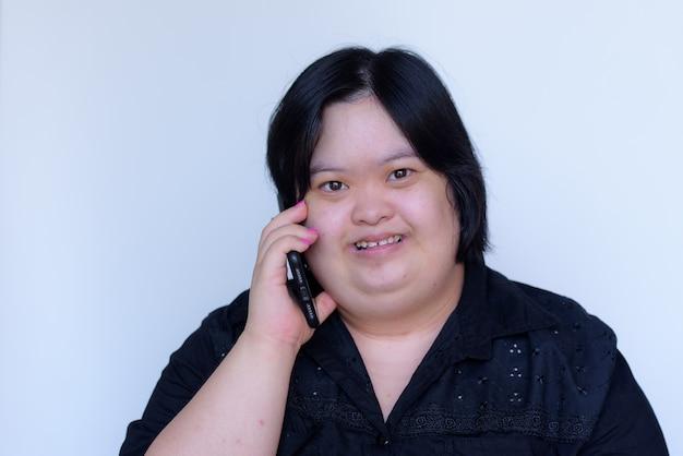 Nahaufnahme eines asiatischen mädchens mit einer behinderung. kinder mit down-syndrom. am telefon sprechen und glücklich auf einem weißen hintergrund lächeln Premium Fotos