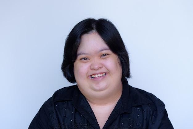 Nahaufnahme eines asiatischen mädchens mit einer behinderung. kinder mit down-syndrom. molliges und niedliches lächeln auf einem weißen hintergrund Premium Fotos
