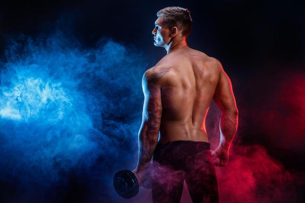 Nahaufnahme eines athletischen stillstehenden mannbodybuilders der hübschen energie während stand mit dummkopf. muskulöser körper der eignung auf dunklem rauchhintergrund. perfekter mann. fantastischer bodybuilder, tätowierung, werfend auf. Premium Fotos