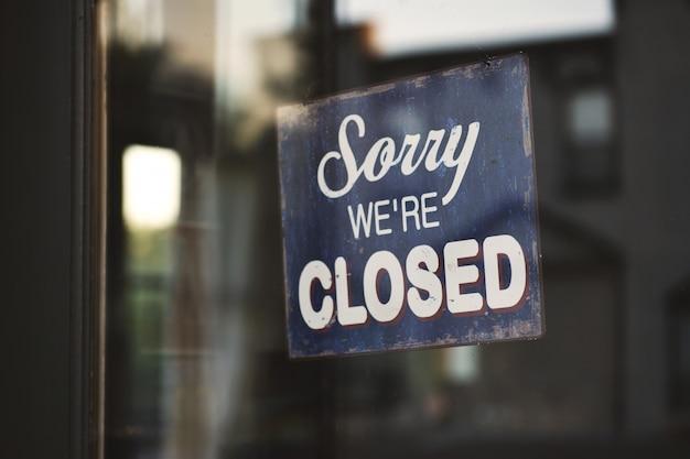 Nahaufnahme eines blauen und weißen entschuldigung, wir sind geschlossene holzbeschilderung auf glas Kostenlose Fotos