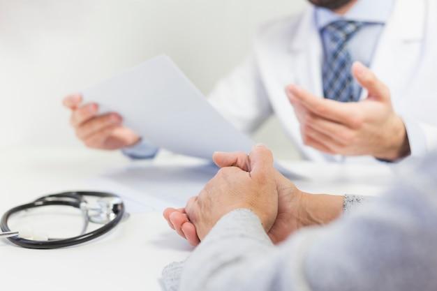 Nahaufnahme eines doktors in seinem büro medizinischen bericht mit patienten besprechend Kostenlose Fotos