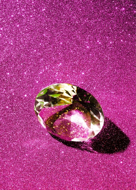 Nahaufnahme eines funkelnden diamanten auf dem rosafarbenen glänzenden hintergrund Kostenlose Fotos