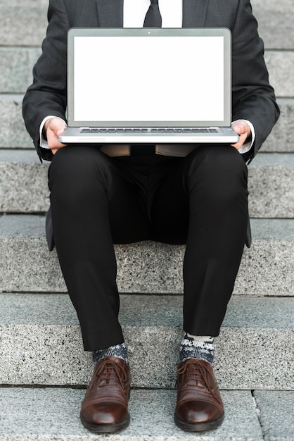 Nahaufnahme eines geschäftsmannes, der auf treppenhäusern mit einem offenen laptop über seinem schoss sitzt Kostenlose Fotos