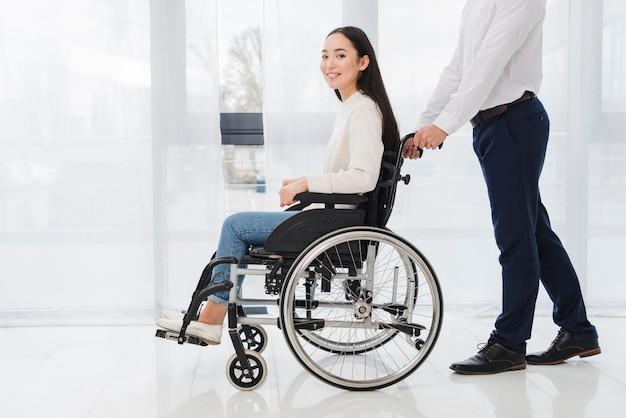 Nahaufnahme eines geschäftsmannes, der die behinderte frau sitzt auf rollstuhl drückt Kostenlose Fotos