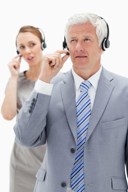 Nahaufnahme eines geschäftsmannes des weißen haares mit einer frau, die im hintergrund beim tragen eines kopfhörers spricht Premium Fotos