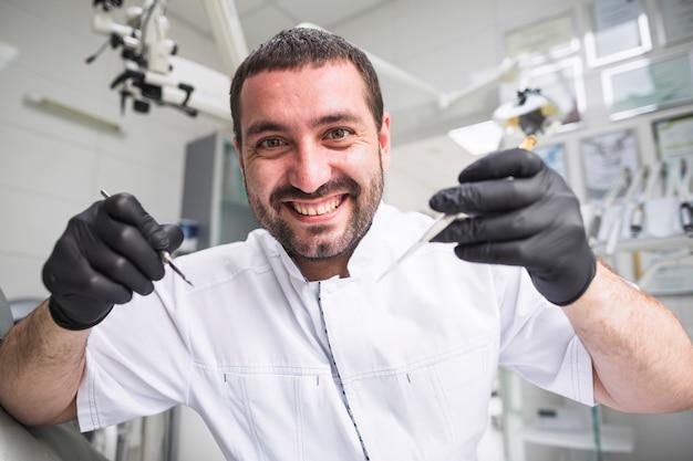 Nahaufnahme eines glücklichen männlichen zahnarztes, der zahnmedizinische werkzeuge hält Kostenlose Fotos
