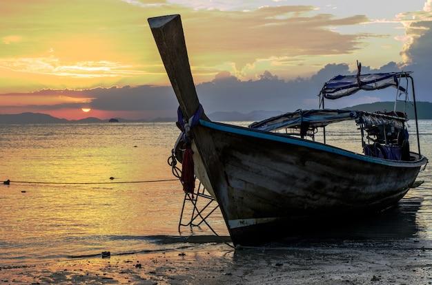 Nahaufnahme eines hölzernen bootes am strand, umgeben vom meer unter einem bewölkten himmel während des sonnenuntergangs Kostenlose Fotos