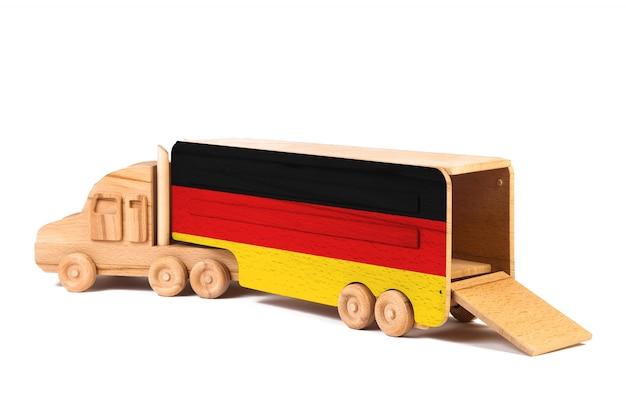 Nahaufnahme eines hölzernen spielzeuglastwagens mit einer gemalten staatsflagge deutschland. das konzept von export-import, transport, nationale zustellung von waren Premium Fotos