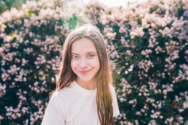 Nahaufnahme eines hübschen lächelnden mädchens, das gegen blumenanlagen steht Kostenlose Fotos