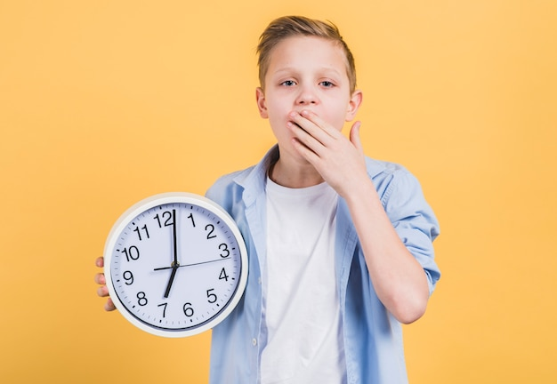 Nahaufnahme eines jungen, der die runde weiße uhr gähnt mit seiner hand auf dem mund steht gegen gelben hintergrund hält Kostenlose Fotos