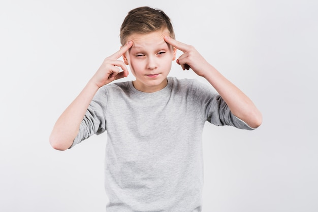 Nahaufnahme eines jungen, der unter kopfschmerzen gegen grauen hintergrund leidet Kostenlose Fotos
