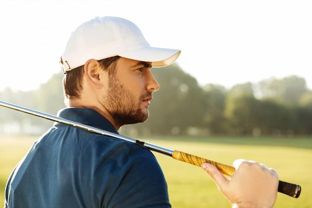 Nahaufnahme eines jungen gutaussehenden männlichen golfspielers im hut Kostenlose Fotos
