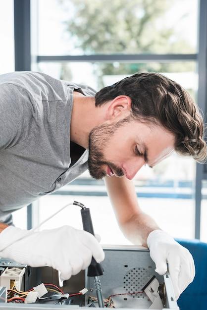 Nahaufnahme eines jungen männlichen technikers, der computer-cpu repariert Kostenlose Fotos