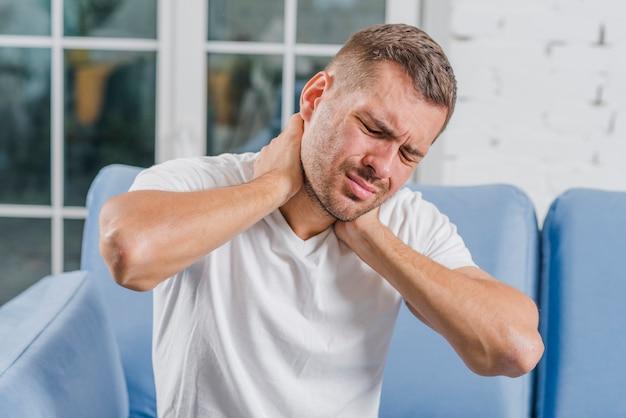 Nahaufnahme eines jungen mannes, der schmerz in seinem hals hat Kostenlose Fotos