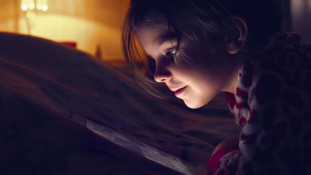 Nahaufnahme eines kleinen netten mädchens in aufpassender tablette der vollen dunkelheit Premium Fotos