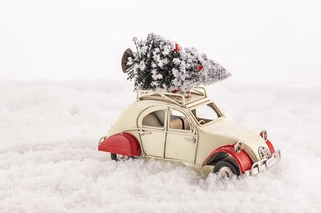 Nahaufnahme eines kleinen vintage-spielzeugautos mit einem weihnachtsbaum auf seinem dach auf einem kunstschnee Kostenlose Fotos