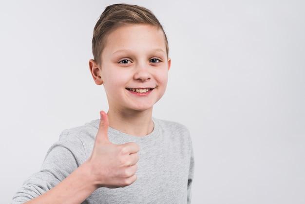 Nahaufnahme eines lächelnden jungen, der daumen herauf das zeichen steht gegen grauen hintergrund zeigt Kostenlose Fotos