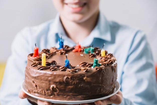 Nahaufnahme eines lächelnden jungen, der den schokoladenkuchen verziert mit bunten kerzen zeigt Kostenlose Fotos