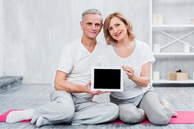Nahaufnahme eines liebevollen paares, das digitale tablette des schwarzen bildschirms hält Kostenlose Fotos