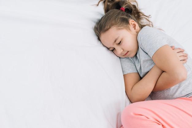 Nahaufnahme eines mädchens, das auf weißem bett mit schmerz schläft Kostenlose Fotos