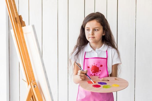 Nahaufnahme eines mädchens, das die farbe mit bürste auf der hölzernen palette betrachtet segeltuch mischt Kostenlose Fotos