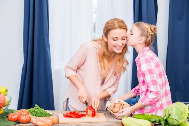 Nahaufnahme eines mädchens, das ihre mutter küsst, die das gemüse mit messer in der küche schneidet Kostenlose Fotos